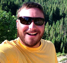 Headshot of Jeremy with sunglasses and evergreen trees in the background