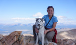 Blog Author Margaux posting a top a mountain with her dog.