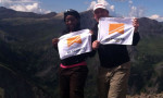 Photo of blog author with teammate at top of mountain. They are holding flags with the logo of No Barriers USA.