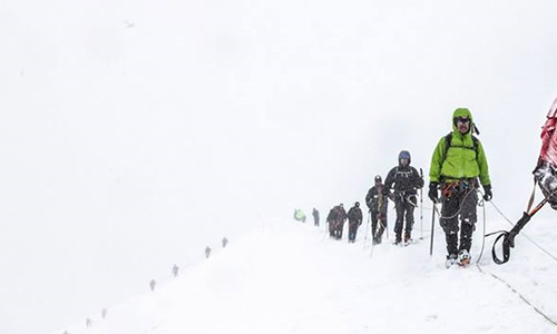 Snowy mountain with a team of climbers roped together, climbing the mountain.
