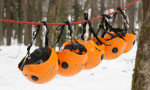 Series of orange climbing helmets hanging on a rope between two trees. Snow is on the ground.