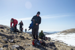 Team member Craig heading to grab his pack after the team takes a break on some rocky terrain. Photo Credit: Rob Jackson