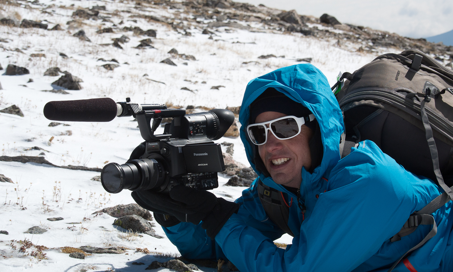 Man in a blue overcoat with hood up, laying on snow, holding a video camera.