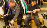 two members of team try on hiking shoes sitting on a bench within a sporting goods store