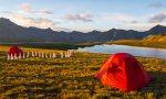 basecamp image showing two orange tents and a sting of flags. mountains and a lake are in the background