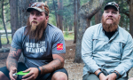 image of two men sitting by a campfire, listening to someone across from them speak