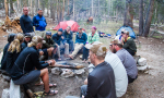 group of people sitting around a campfire