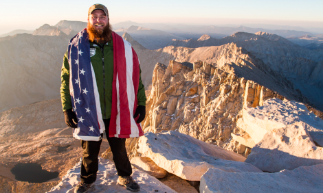 man stands a top mountain with american flag draped over his arms